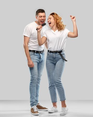 relationships and people concept - happy couple in white t-shirts singing to hairbrush over grey background