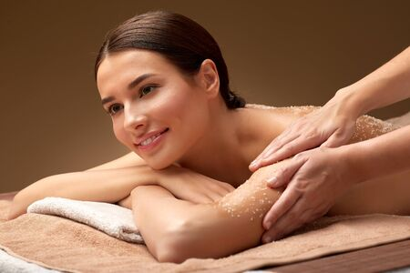 wellness, beauty and relaxation concept - happy young woman having exfoliating salt massage at spa Stock Photo