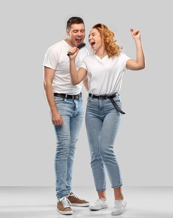 feliz pareja cantando al cepillo para el cabello Foto de archivo