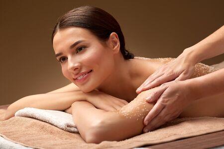 happy woman having exfoliating salt massage at spa Stock Photo