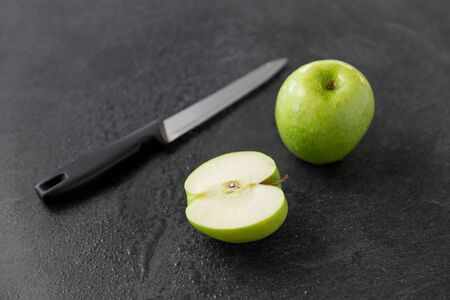 green apples and kitchen knife on slate background