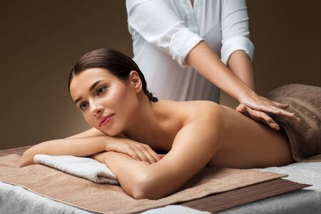 wellness, beauty and relaxation concept - beautiful young woman lying and having back massage at spa Stock Photo
