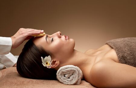 beauty, pampering and relaxation concept - close up of beautiful young woman lying with closed eyes and having face massage with sponge in spa