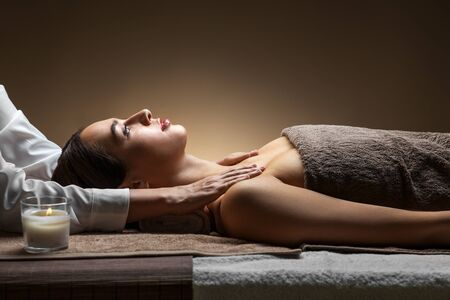 wellness, beauty and relaxation concept - beautiful young woman lying with closed eyes and having face and head massage at spa Imagens