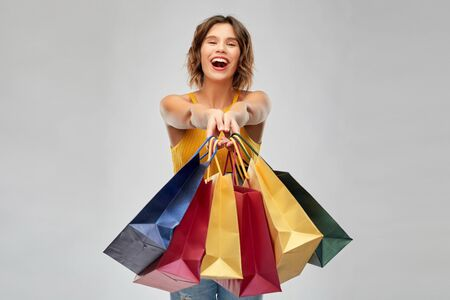sale and people concept - happy smiling young woman in mustard yellow top and jeans with shopping bags over grey background