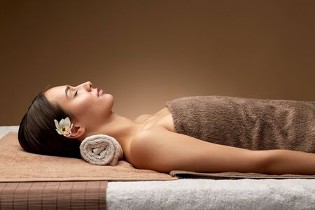 young woman lying at spa or massage parlor Фото со стока - 133683795