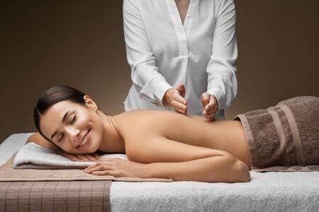 woman lying and having back massage at spa Stock Photo