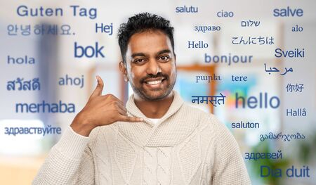 indian man in sweater making phone call gesture