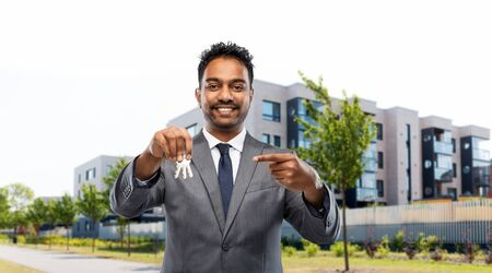 indian man realtor with home keys on city street Banco de Imagens