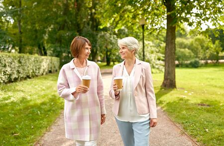 senior women or friends drinking coffee at park Banco de Imagens