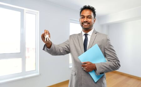 indian man realtor with key and folder at new home