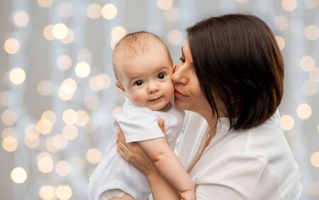 gelukkige moeder die kleine baby kust over lichten Stockfoto