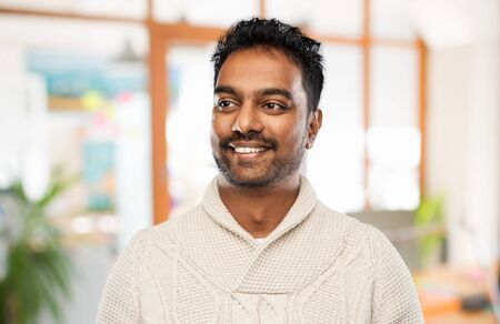 indian man in sweater over office background