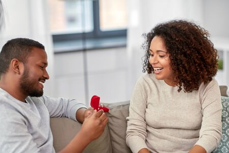 african american man giving woman engagement ring