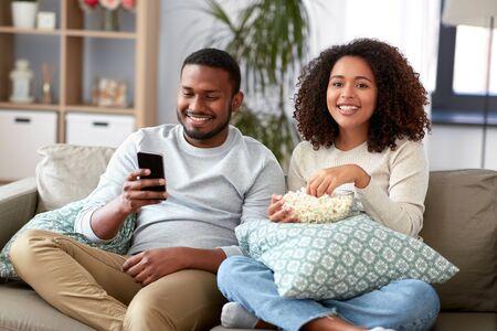 Pareja africana con palomitas de maíz viendo la televisión en casa