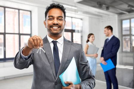 indian man realtor with keys at empty office room