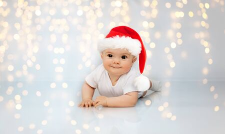 little baby in santa helper hat lying on floor