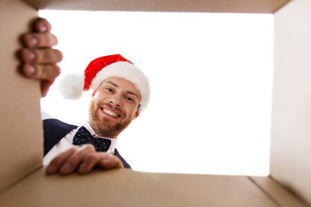 happy young man looking into open christmas gift