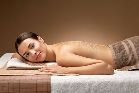 woman lying with sea salt on skin at spa Stock Photo