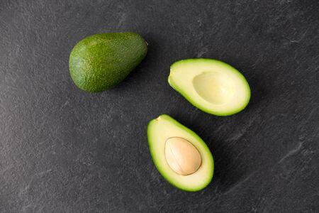 close up of ripe avocado on slate stone background
