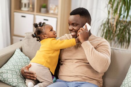 father with baby at home calling on smartphone