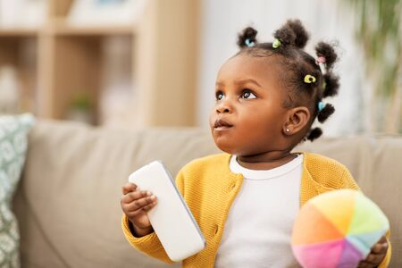 african american baby girl with smartphone at home Banco de Imagens