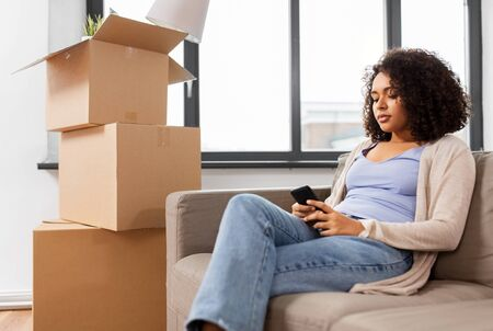 woman with smartphone and boxes moving to new home Stock fotó
