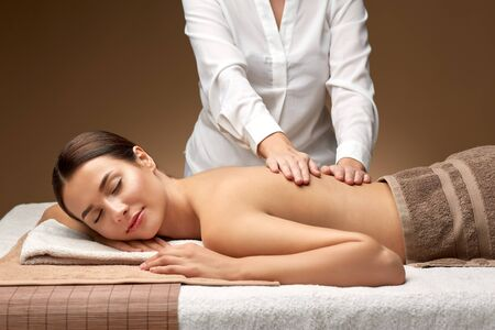 woman lying and having back massage at spa Stock Photo - 133932324