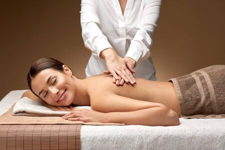 woman lying and having back massage at spa Imagens