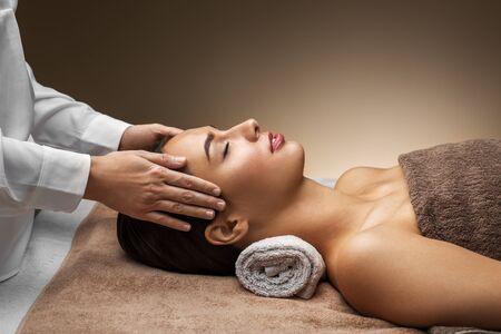 woman having face and head massage at spa
