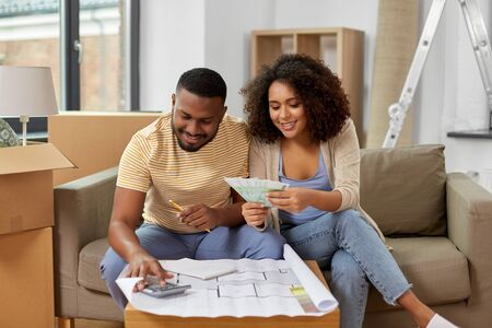 couple with blueprint counting money at home