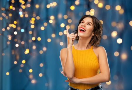 gesture, idea and people concept - happy smiling young woman in yellow top pointing finger up over festive lights on dark blue background Banco de Imagens