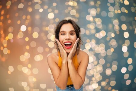 emotions, expressions and people concept - surprised young woman in yellow top over festive lights background Banco de Imagens
