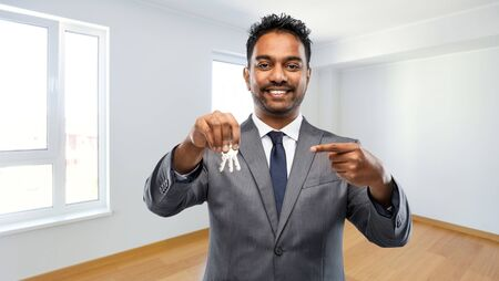 real estate business and people concept - indian man realtor with keys over empty new apartment room background Banco de Imagens