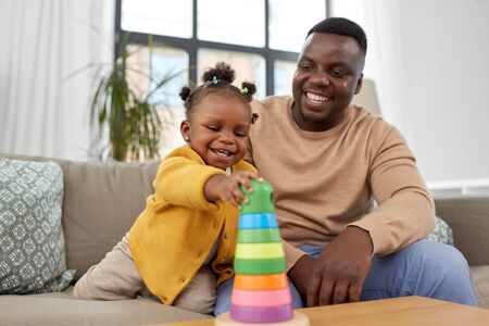 family, parenthood and people concept - happy african american father and baby daughter playing with toy blocks at home