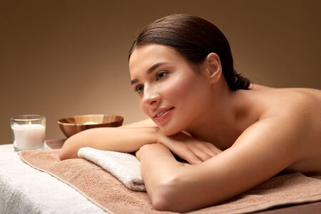 wellness, beauty and relaxation concept - young woman lying at spa or massage parlor