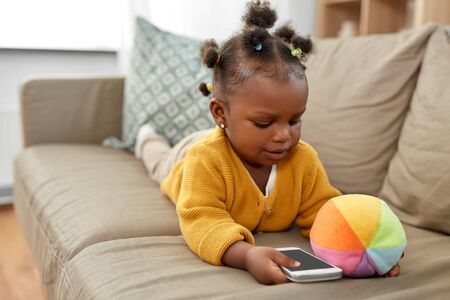 children and technology concept - lovely african american baby girl with smartphone and toy ball at home