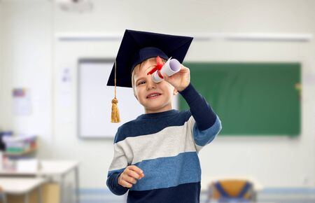 little boy in mortarboard looking through diploma 写真素材