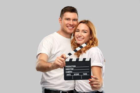 happy couple in white t-shirts with clapperboard