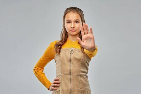 teenage girl making stopping gesture