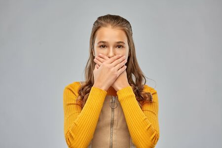 scared teenage girl closing her mouth by hands