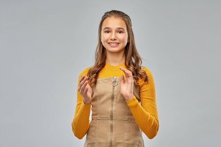 smiling teenage girl applauding on grey background