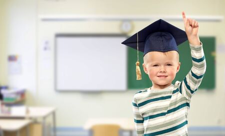 boy in mortar board pointing finger up at school