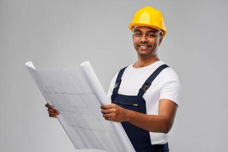 happy indian builder in helmet with blueprint