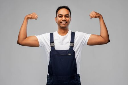 smiling indian worker or builder showing his power