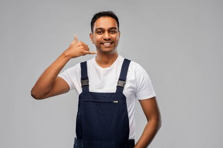 profession, construction and building - happy smiling indian worker or builder making phone call gesture over grey background