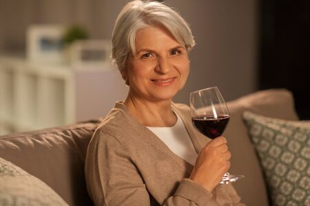 people, alcohol and drinks concept - happy smiling senior woman drinking red wine from glass at home in evening