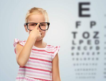 smiling little girl in glasses over eye test chart