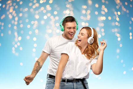 happy couple in headphones dancing