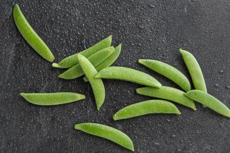 peas on wet slate stone background